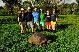 Students from the BIOL 4506 course next to a giant tortoise